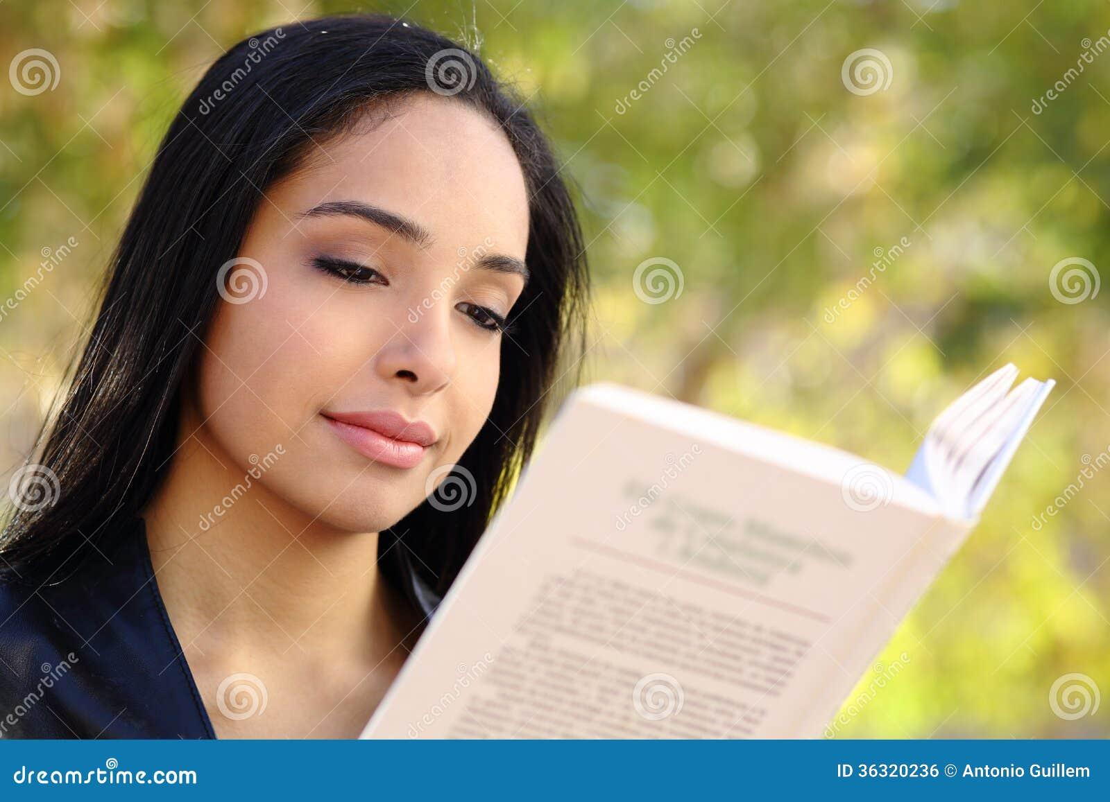 Закройте вверх красивой женщины читая книгу в парке