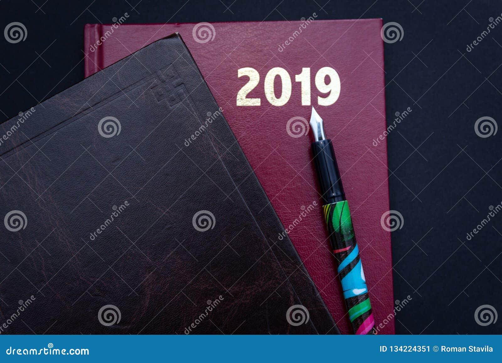 Закройте вверх 2019 красного и коричневых кожаных diarys с авторучкой