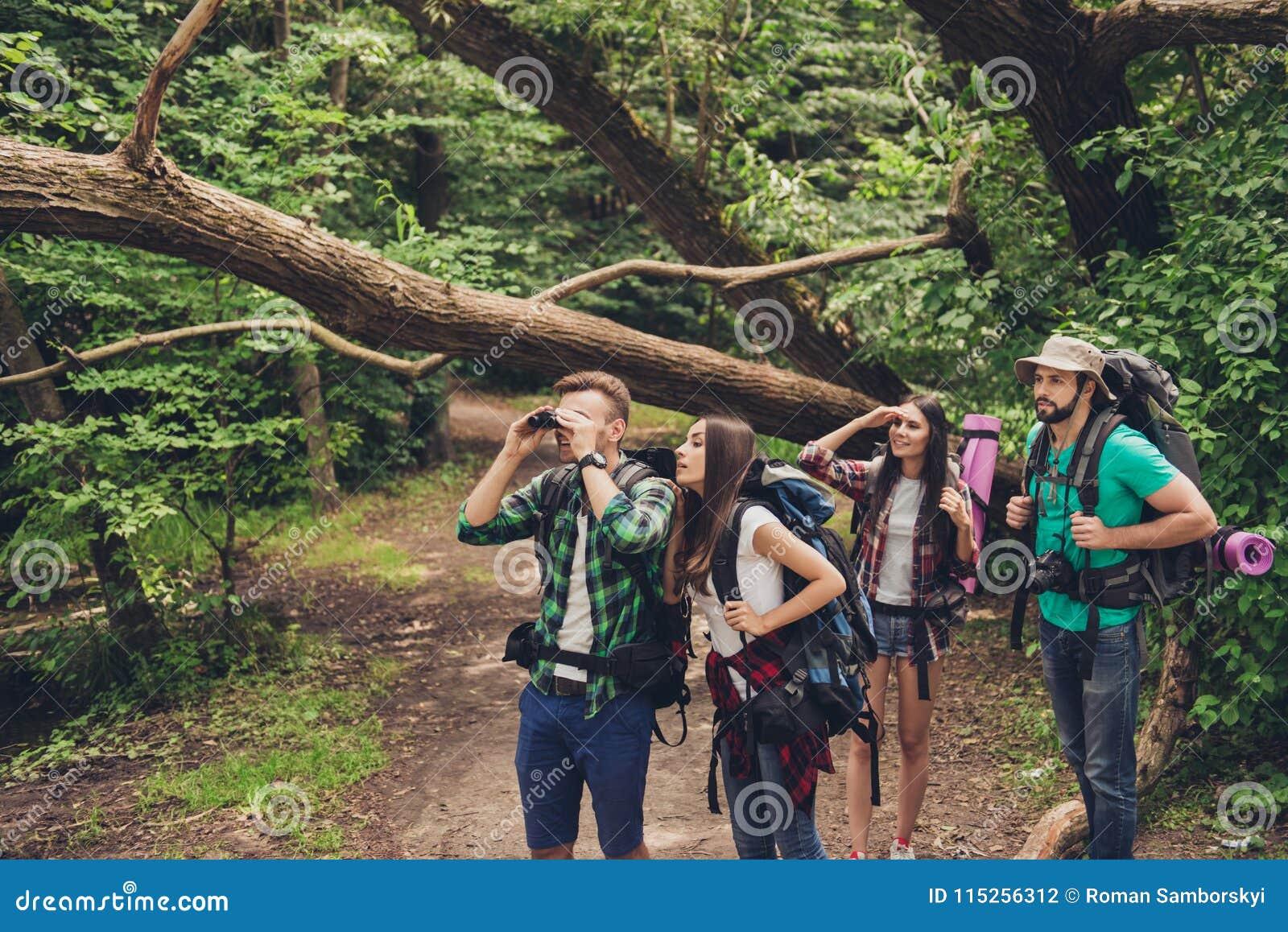 Закройте вверх 4 лучших другов, идущ в лес осени, изумленный красотой природы, нося удобные обмундирования для пешего туризма,
