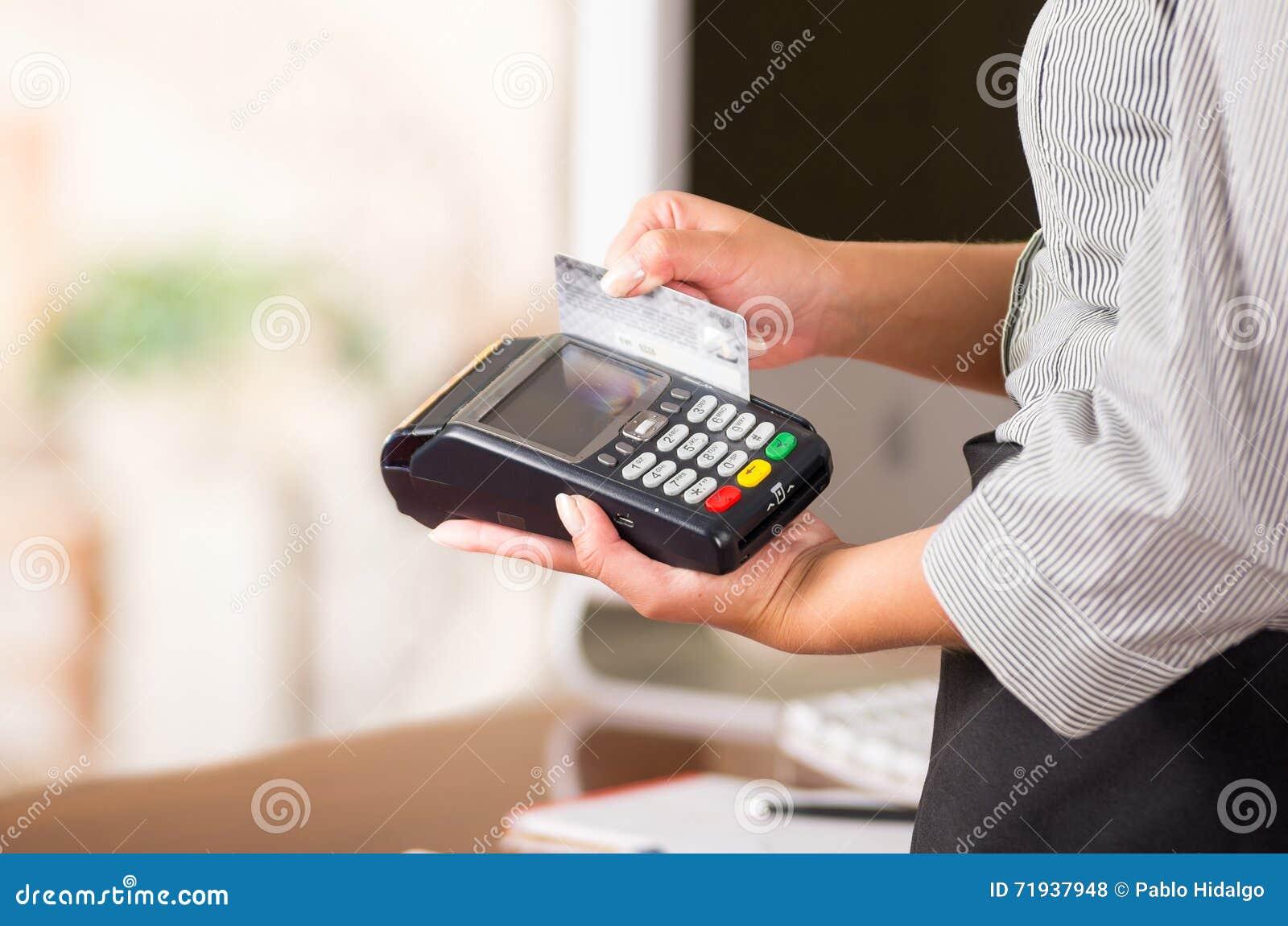Закройте вверх машины кредитной карточки, руки женщины swaping серая карточка