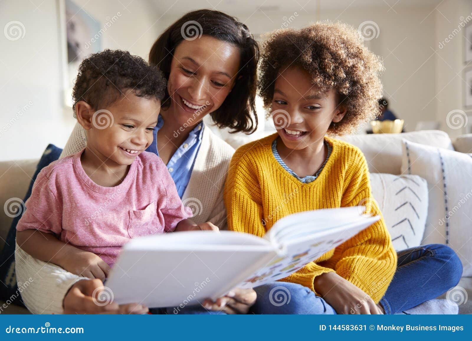 Закройте вверх молодой матери сидя на софе в живущей комнате с ее детьми, читающ их книга, низкий угол