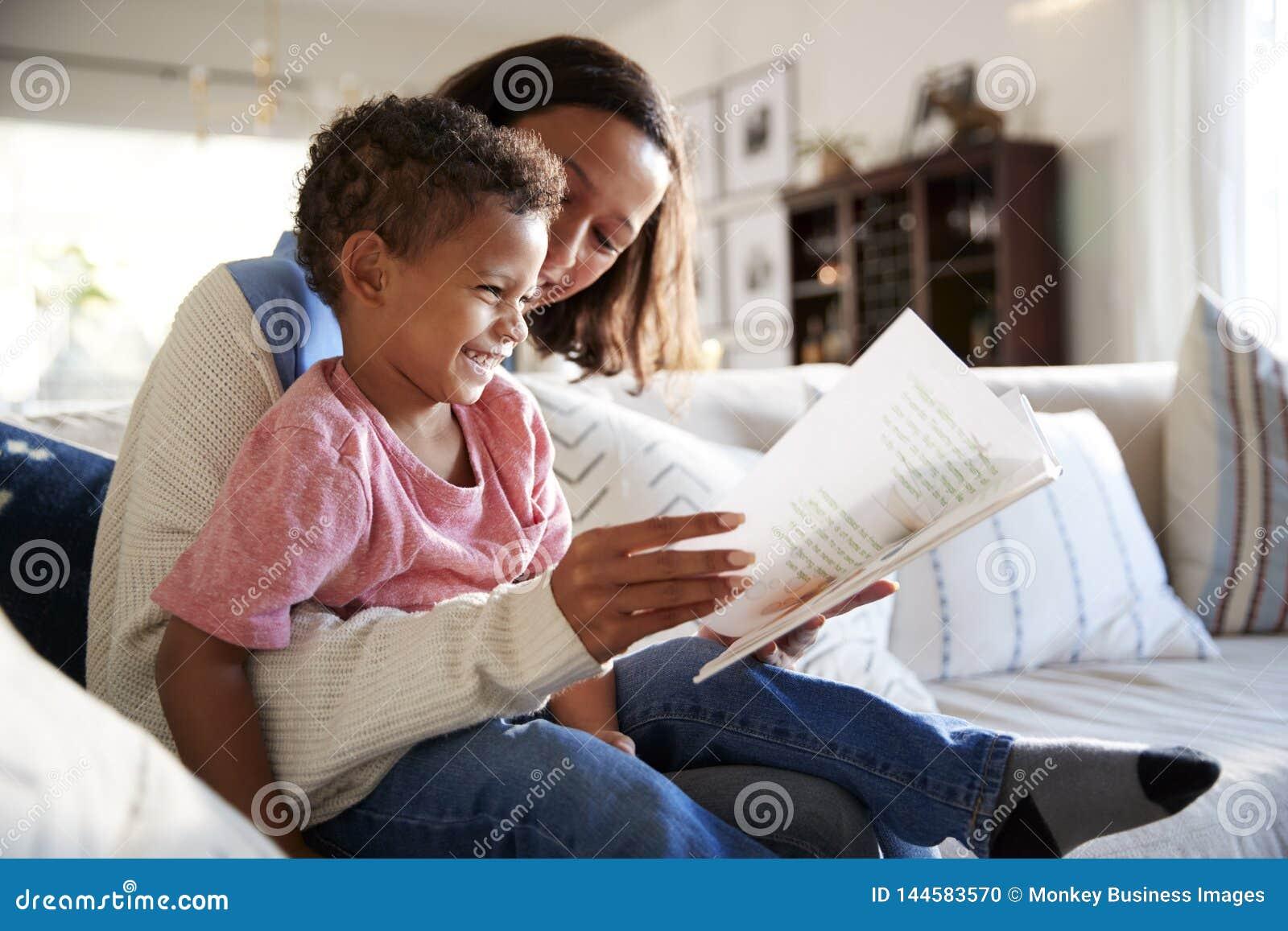 Закройте вверх молодой матери сидя на софе в живущей комнате читая книгу с ее сыном малыша, который сидит на ее колене, sid