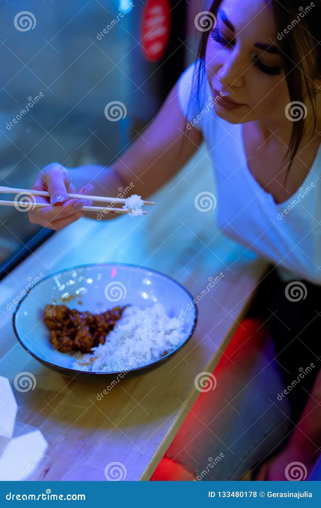 Закройте вверх молодой привлекательной женщины есть азиатскую еду с палочками на кафе