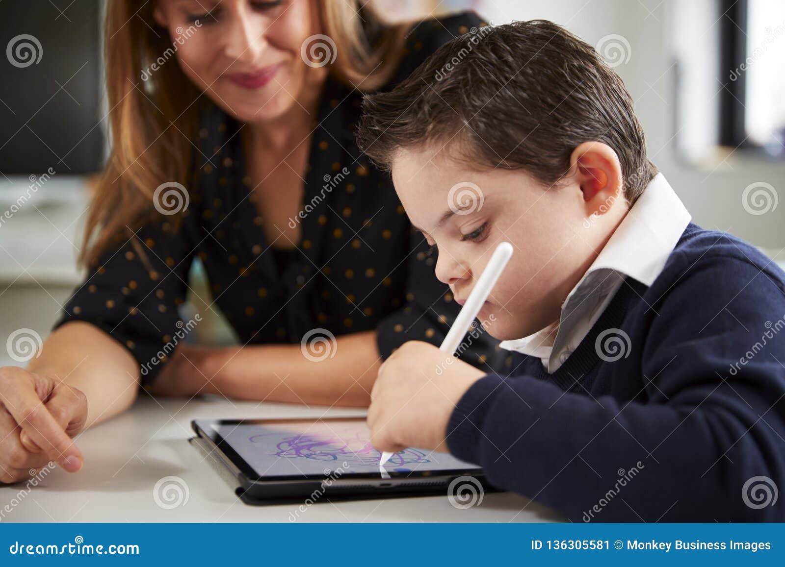 Закройте вверх молодой учительницы сидя на столе со школьником Синдрома Дауна используя планшет в classr начальной школы