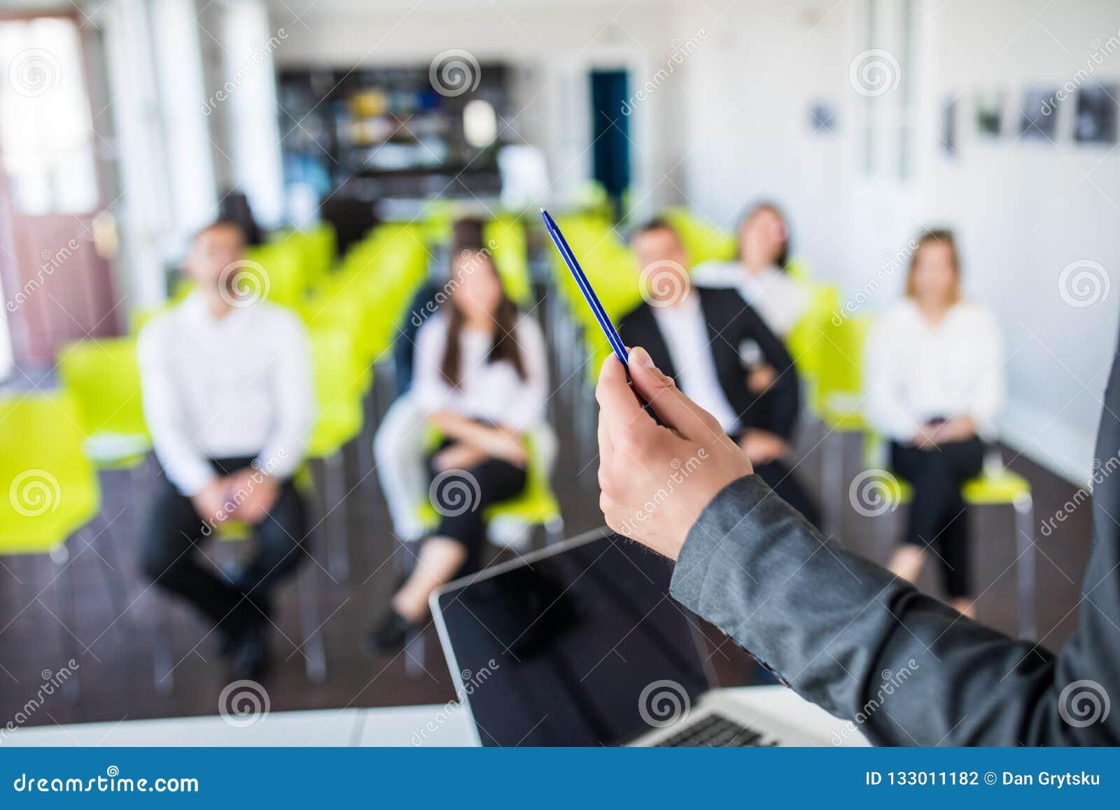 Закройте вверх мужского ментора или обработка документов владением тренера, дает представление flipchart, разговаривая с работник