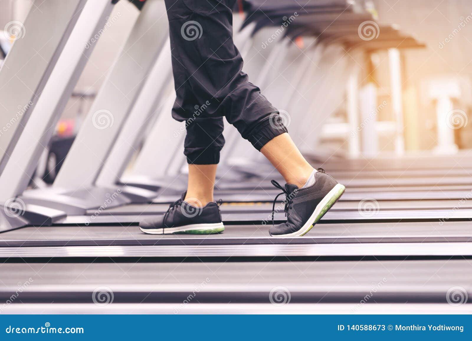 Закройте вверх на ботинке, тренировке женщины с ногами бежать на третбане и сгорите сало в теле в спортзале, здоровом образе жизн