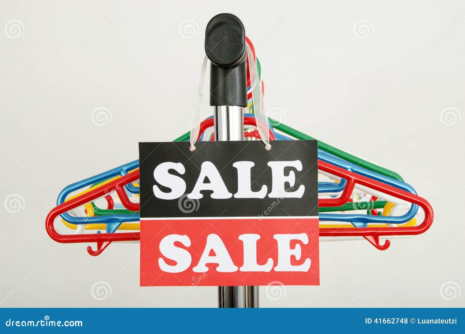 Закройте вверх на пустых вешалках и большом знаке продажи