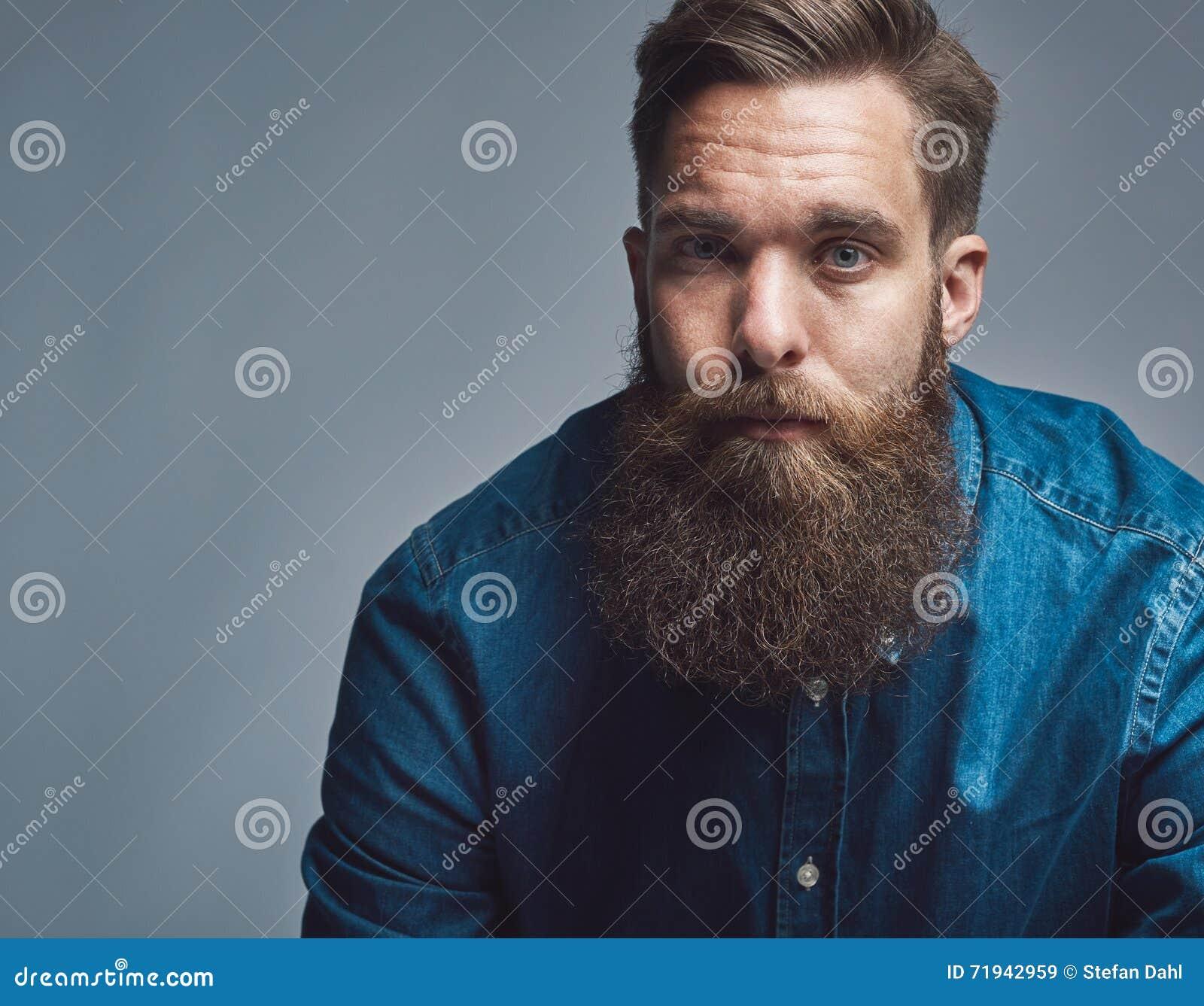 Закройте вверх на серьезном человеке в голубых рубашке и бороде
