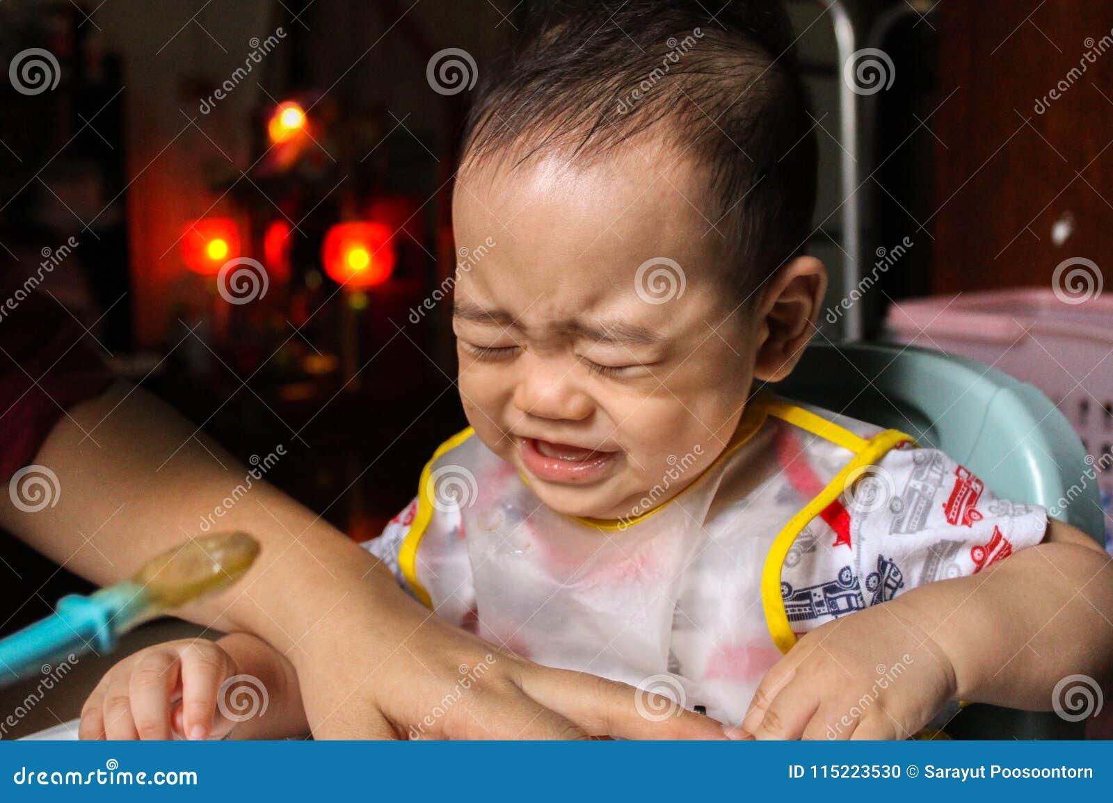 Закройте вверх несчастных маленьких 7 месяцев старого сына внутри видеть до конца пластичный bib кричащий и плача в стуле для мла