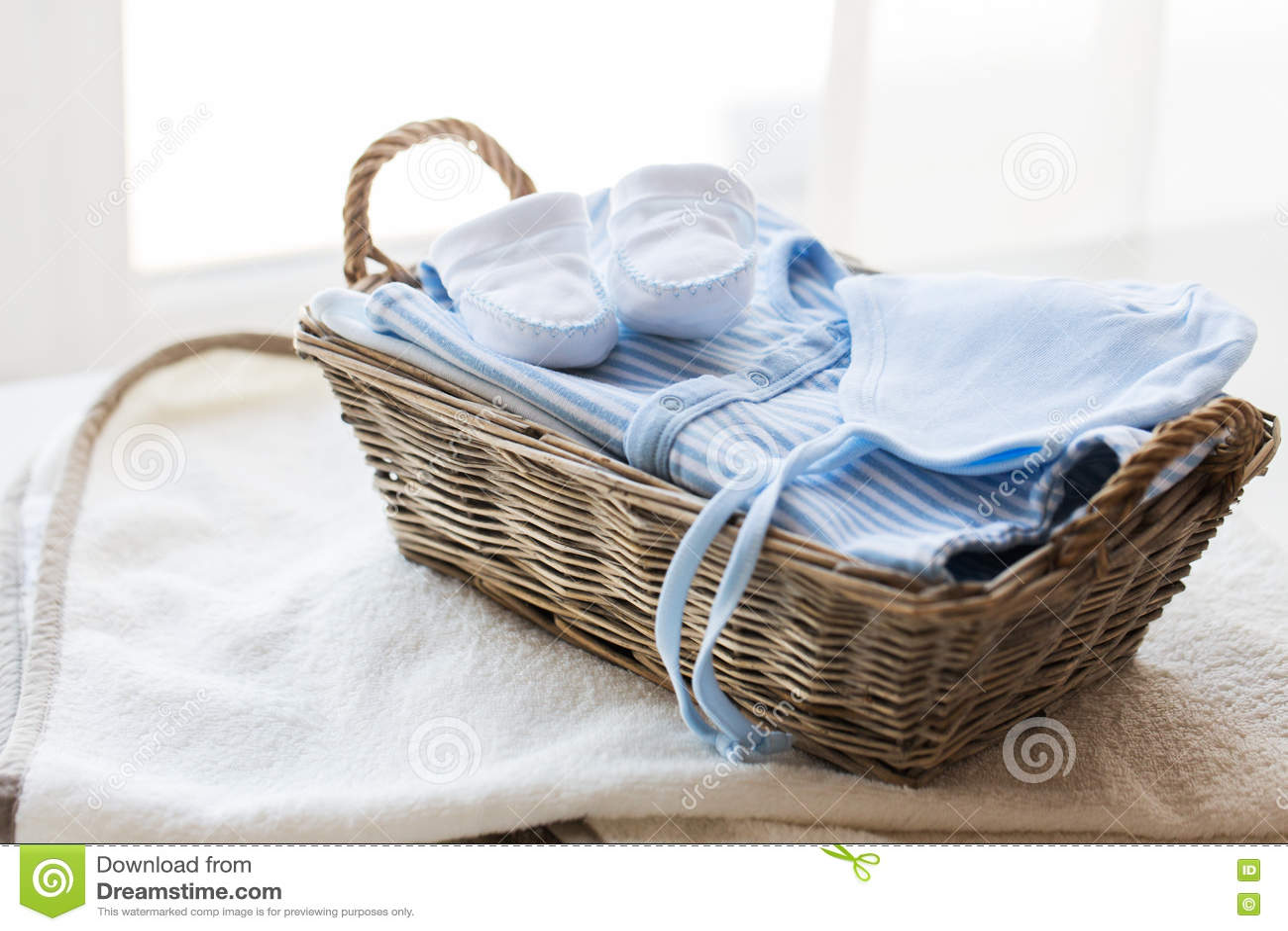 Закройте вверх одежд младенца для newborn мальчика в корзине