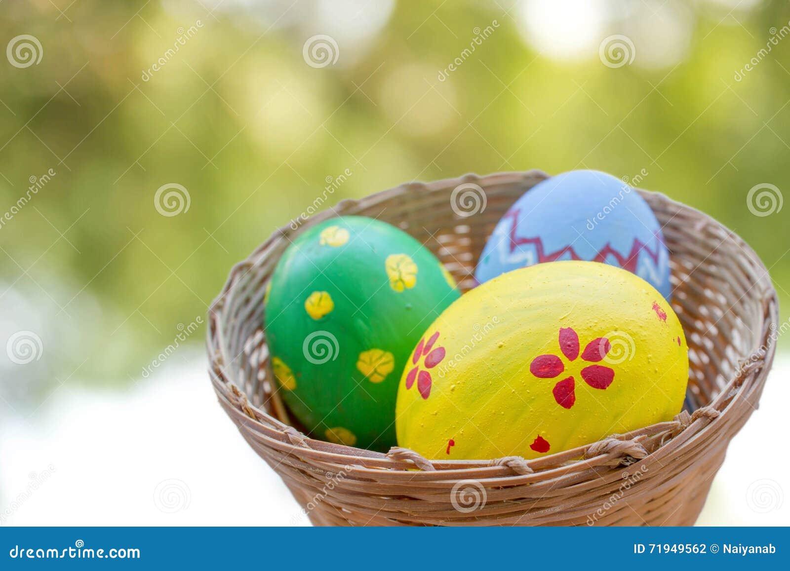 Закройте вверх покрашенных пасхальных яя в корзине