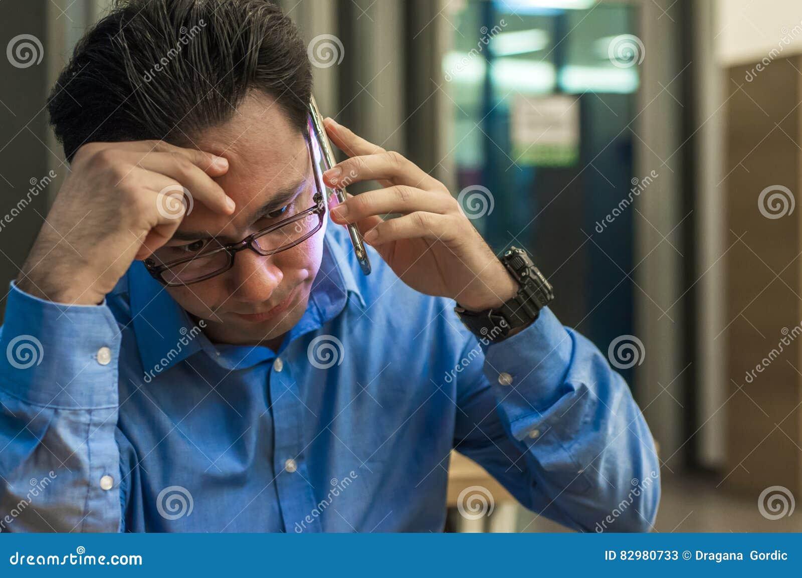 Закройте вверх подавленного и разочарованного бизнесмена на телефоне плохая новость Потревоженный молодой бизнесмен