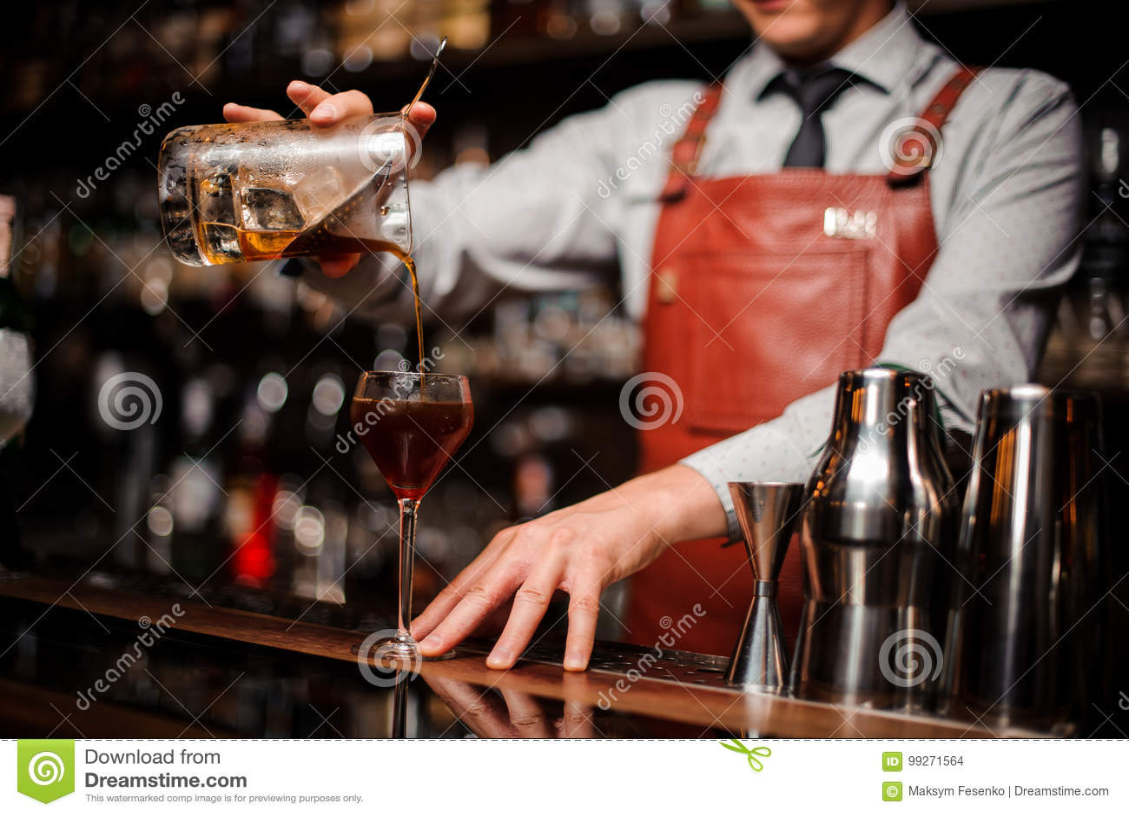 Закройте вверх по бармену лить яркий красный коктеиль спирта в причудливое стекло