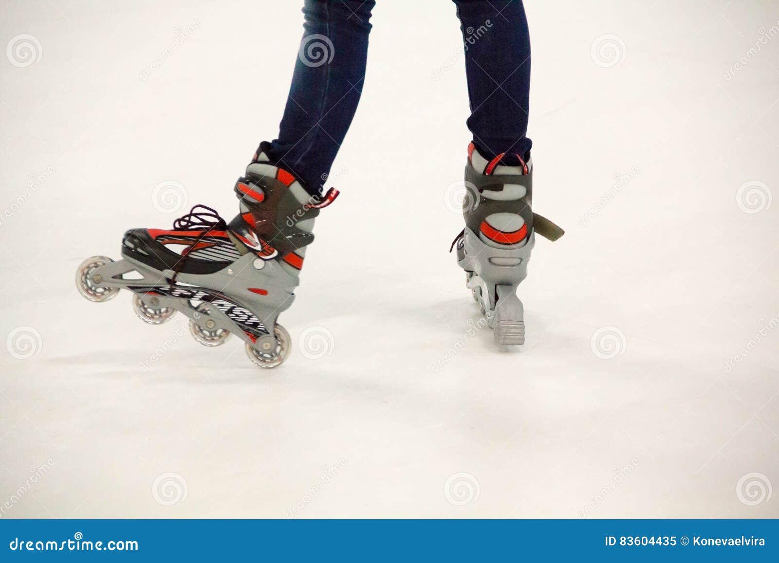 Закройте вверх по взгляду, на белизне, встроенных конька или rollerblade на катке