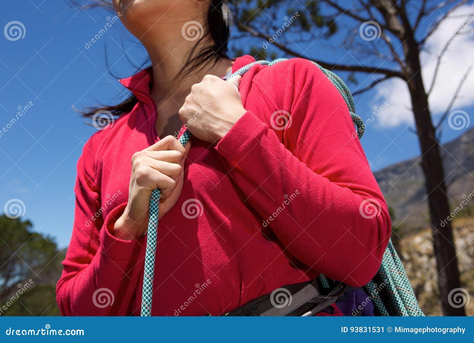 Закройте вверх по женскому альпинисту держа моток веревочки outdoors