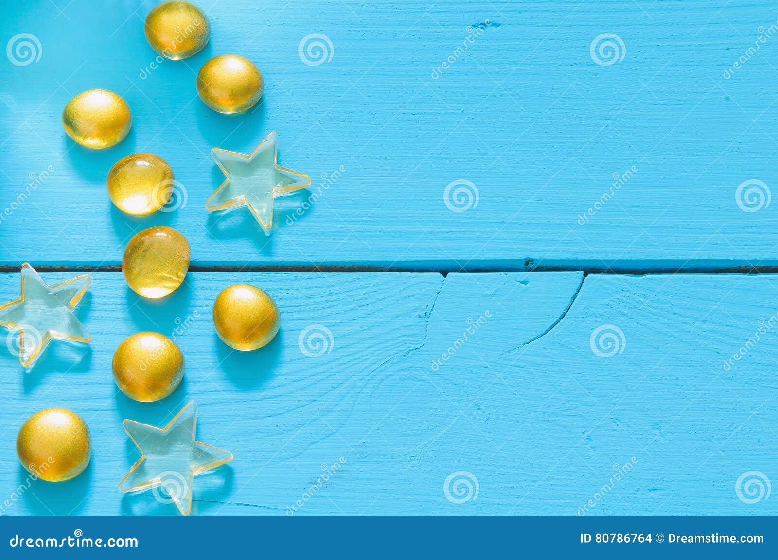 Закройте вверх по изображению желтых мраморов на голубой деревянной предпосылке