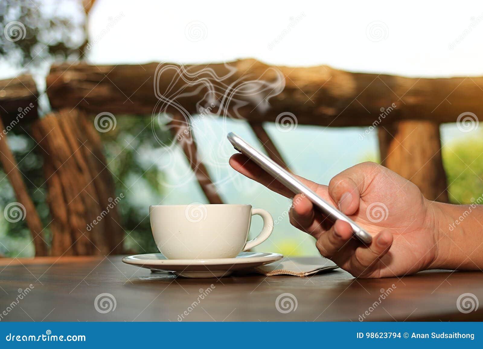 Закройте вверх по кофейной чашке при руки молодого человека держа мобильный телефон в предпосылке природы Селективный фокус и мал