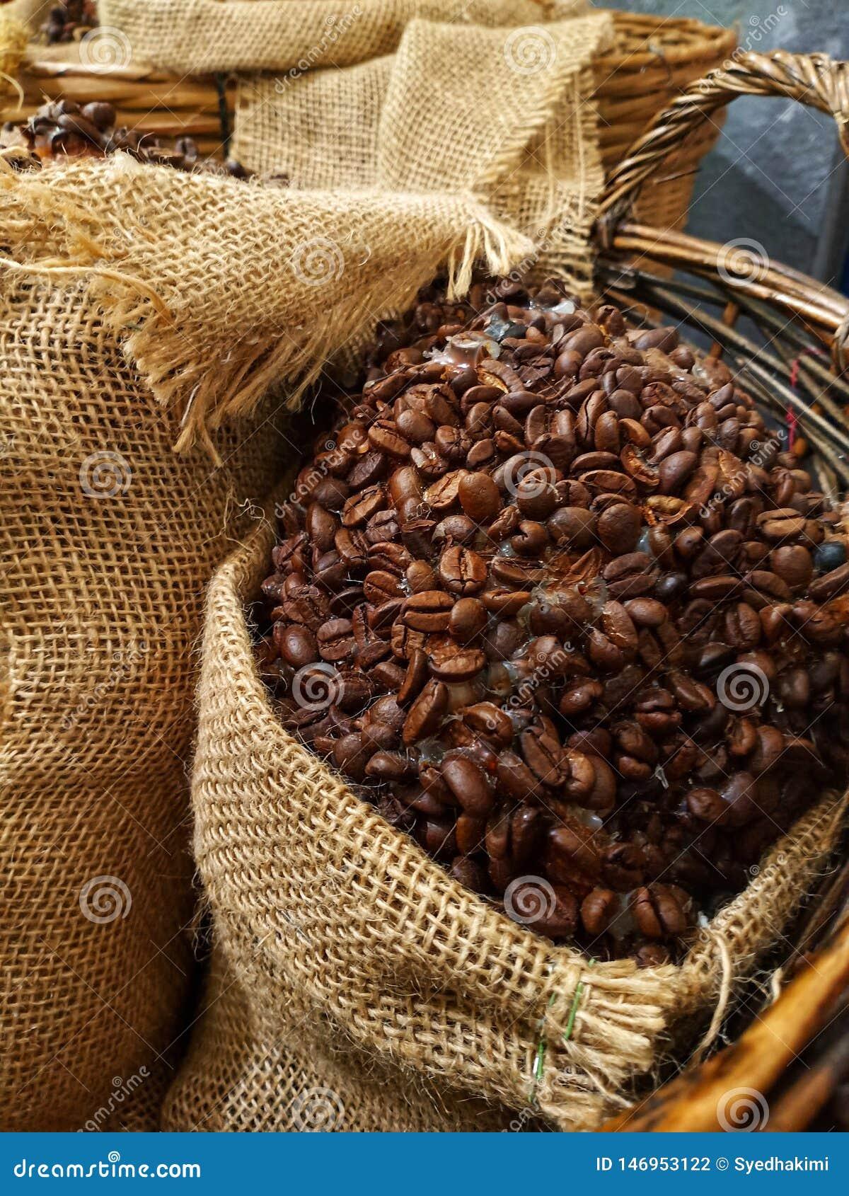 Закройте вверх по кофейным зернам в дерюге в корзине