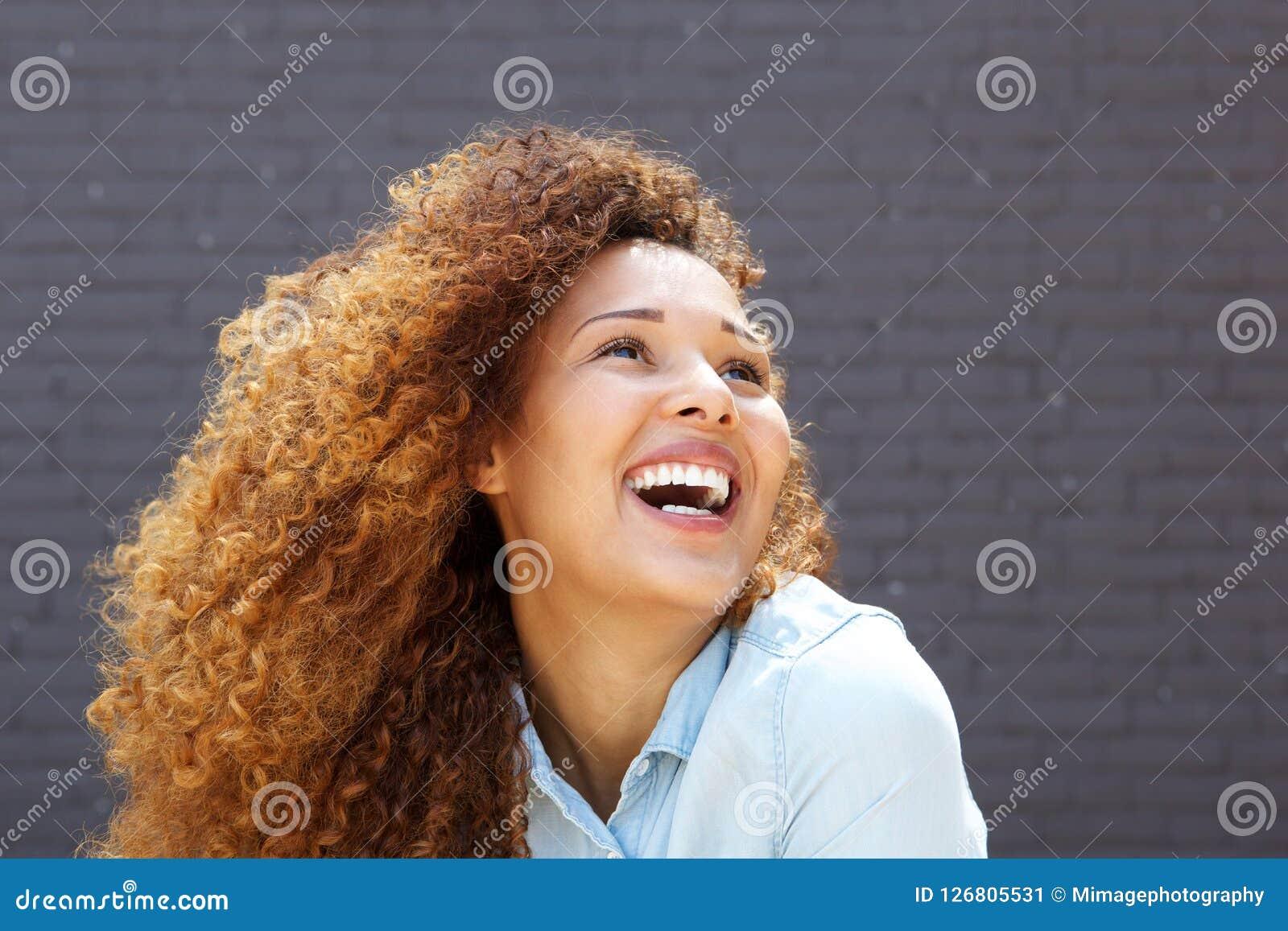 Закройте вверх по красивой молодой женщине с вьющиеся волосы усмехаясь и смотря вверх