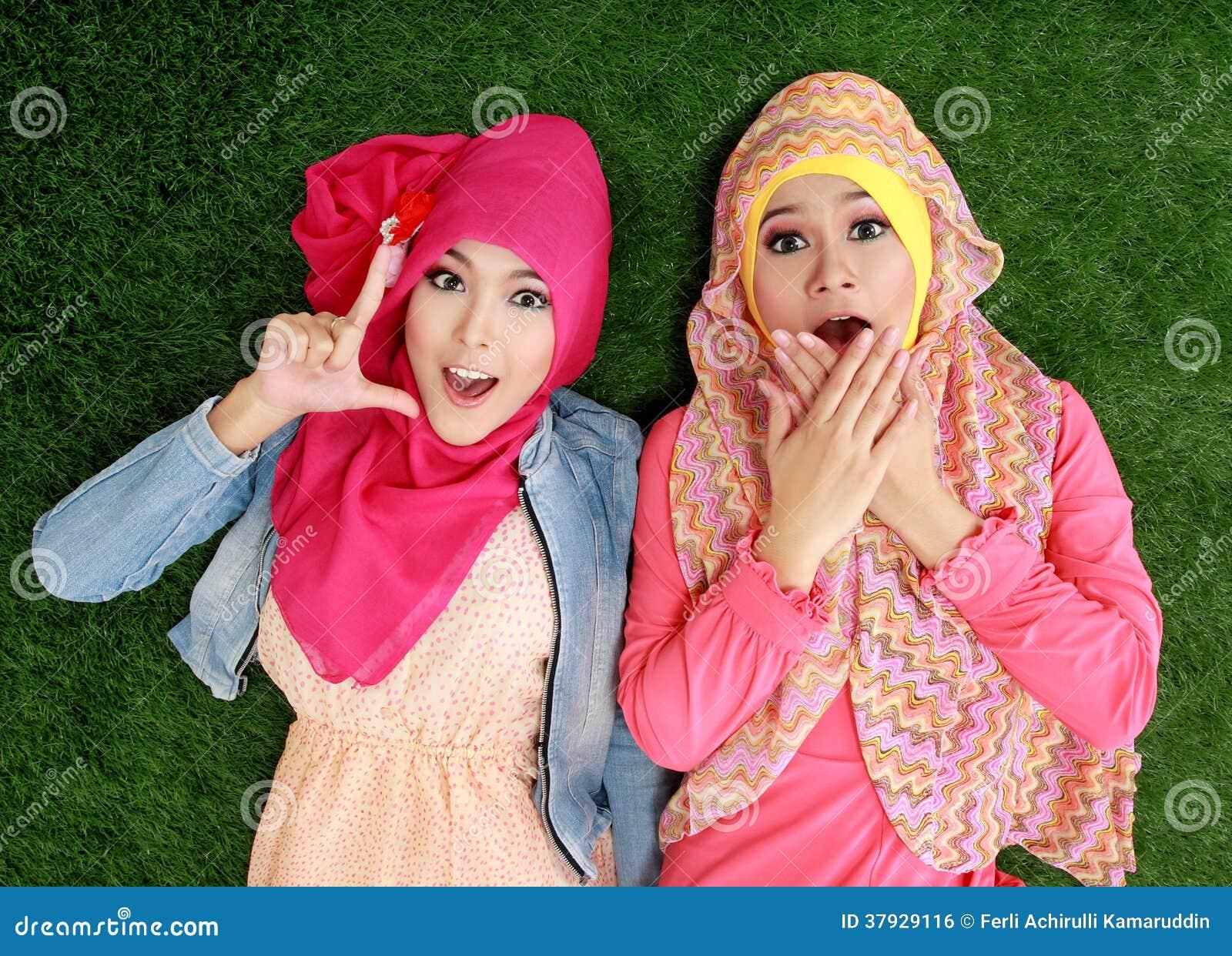 Закройте вверх по красивой счастливой мусульманской женщине 2 лежа на траве