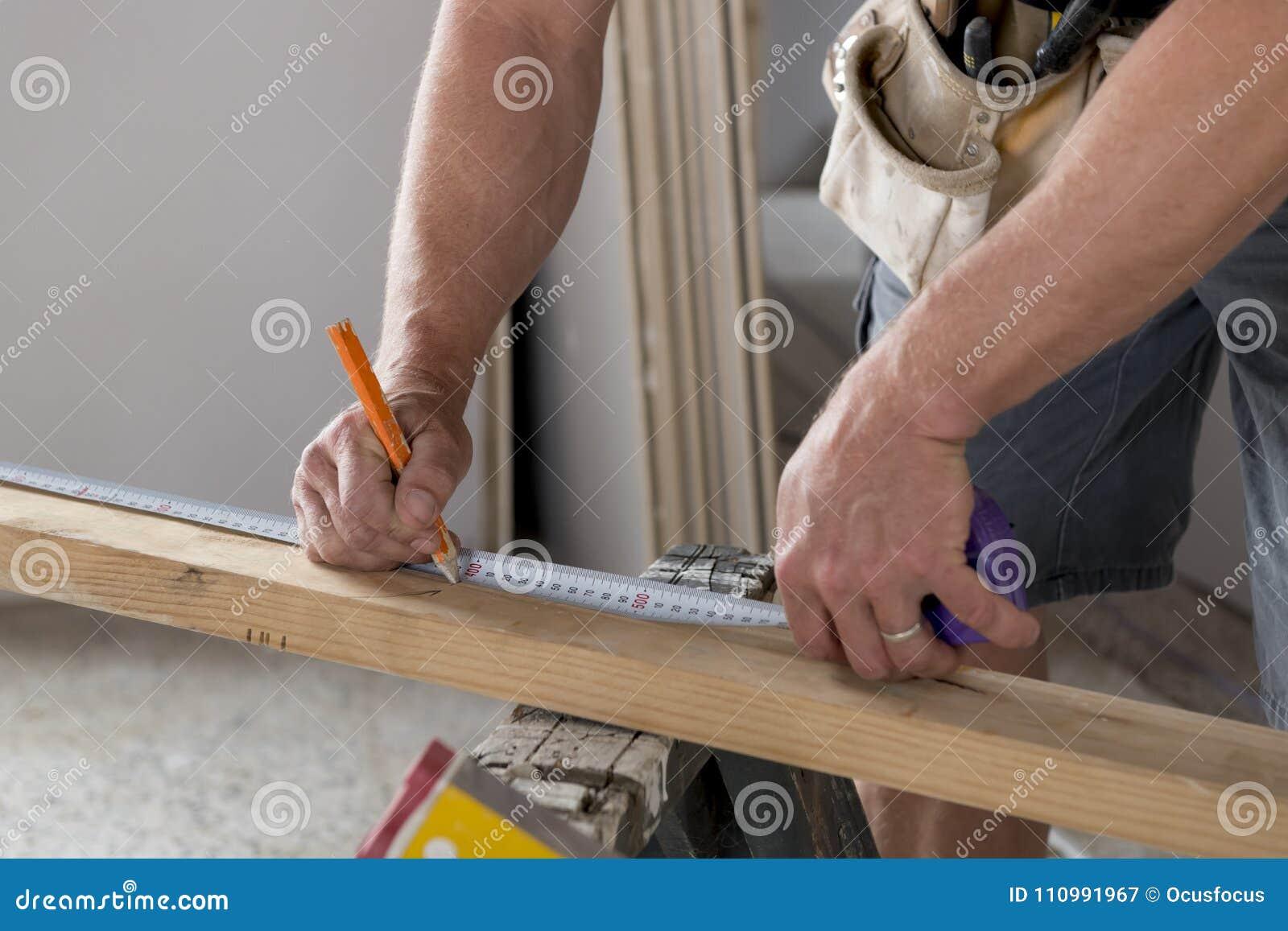 Закройте вверх по мужскому плотнику конструктора или древесине детали рук построителя работая и измеряя в концепции работы индуст