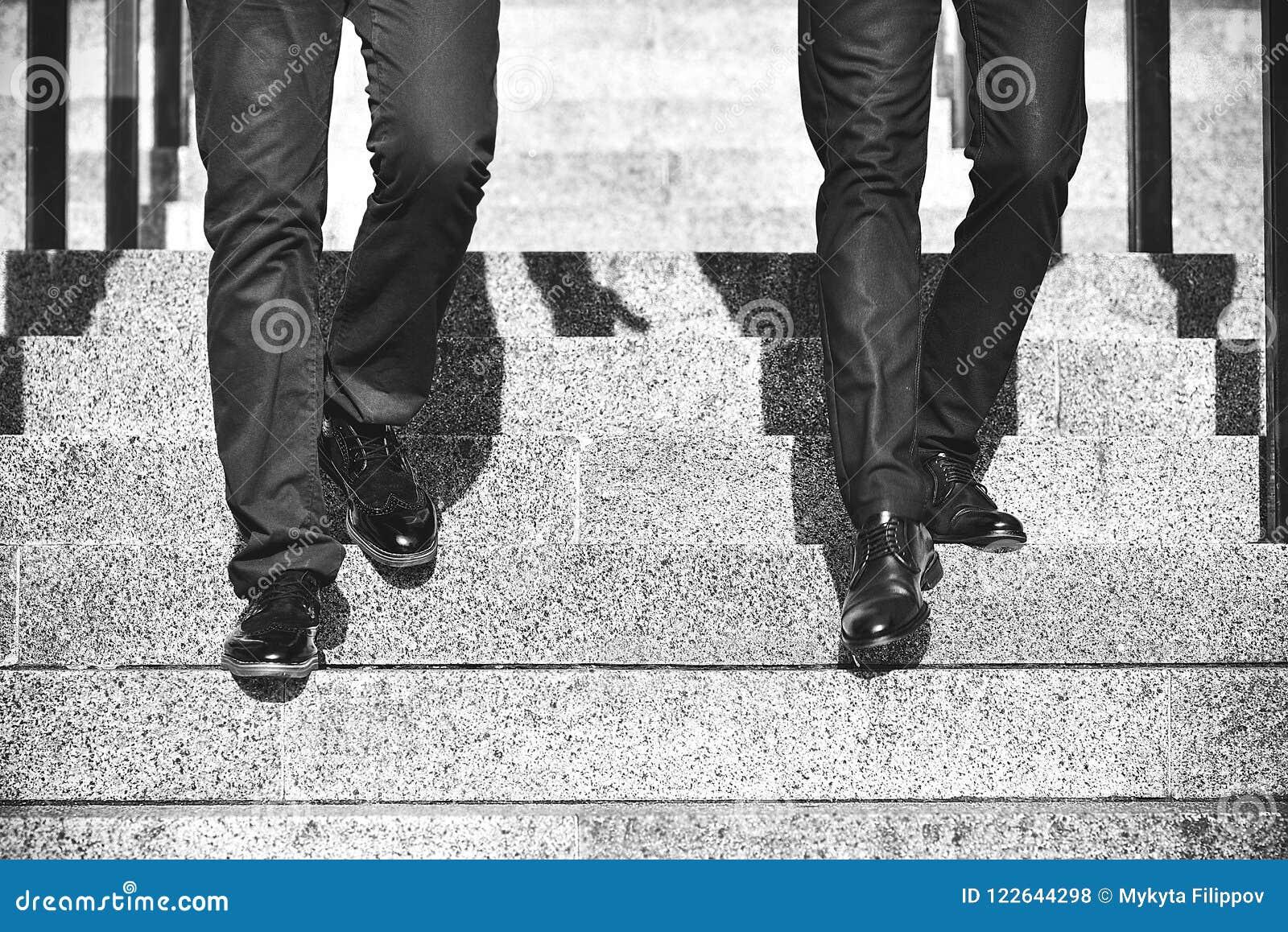 Закройте вверх по ногам бизнесмена 2 идя вниз с лестницы в современном городе