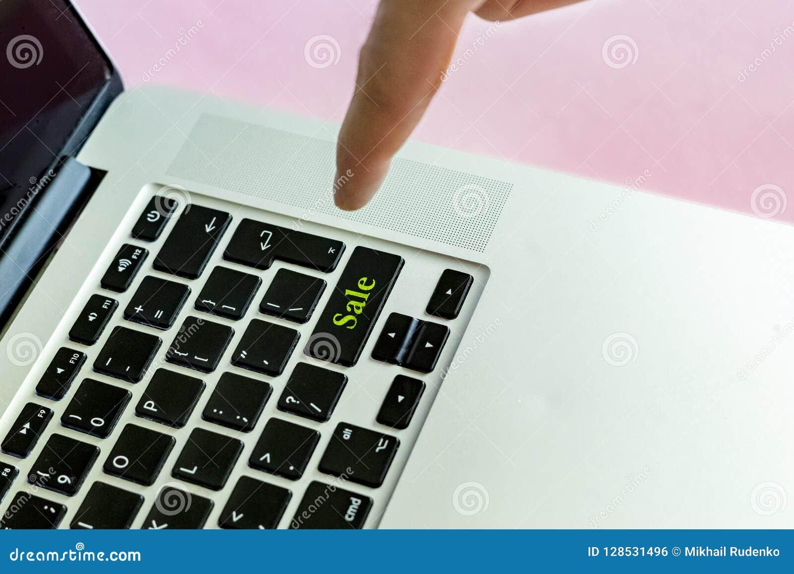 Закройте вверх по пальцу руки ` s персоны нажимая текст ` продажи ` на кнопке концепции изолированной клавиатурой v компьтер-книж