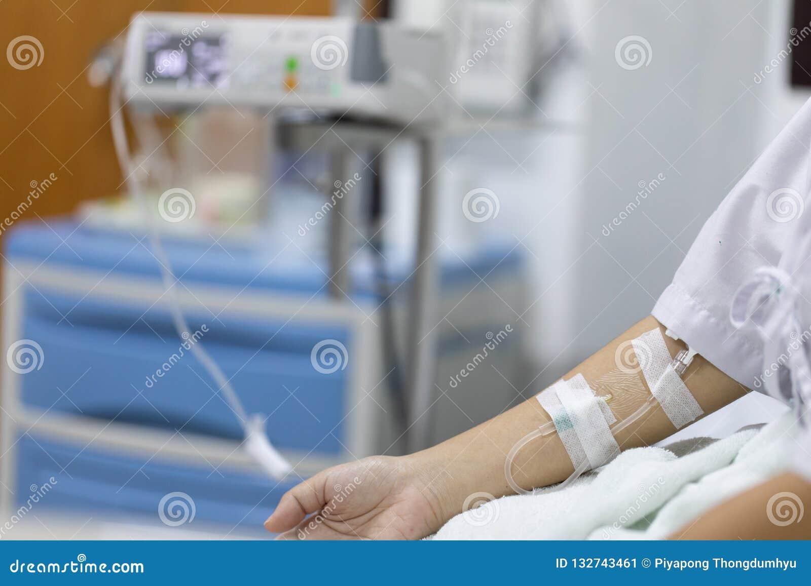 Закройте вверх по пациенту женщины руки с впрыской соляной в руке и во время лежа кроватей реабилитации больница