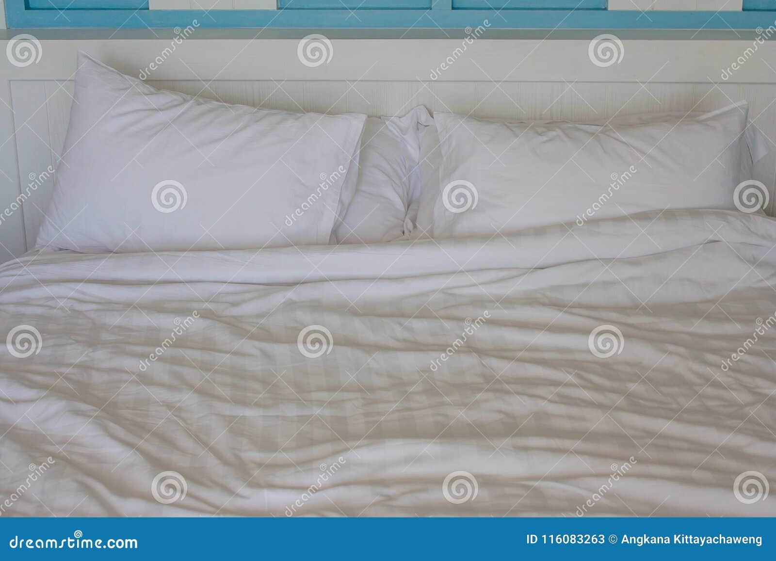 Закройте вверх по 2 подушке скомканной белизнами на кровати в спальне