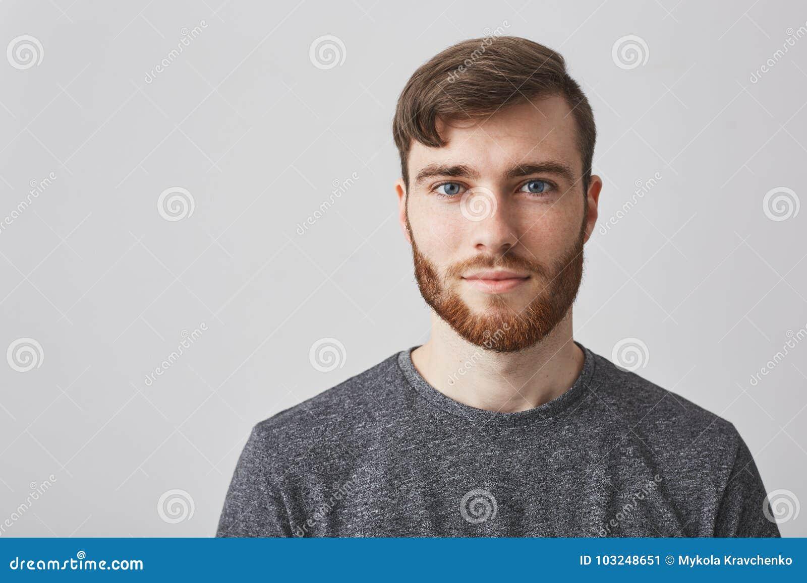 Закройте вверх по портрету красивого мужественного бородатого парня с стильным стилем причёсок усмехаясь, смотрящ в камере с счас