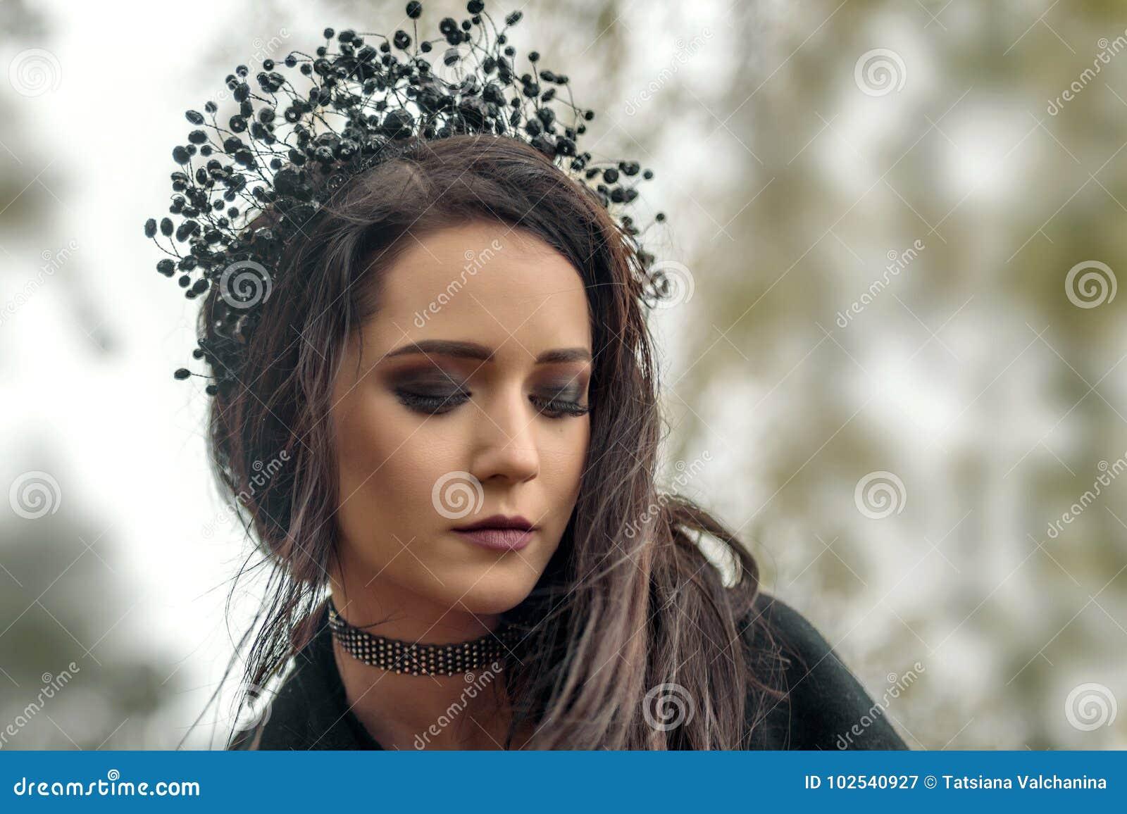 закройте вверх по портрету маленькой девочки в изображении черной ведьмы ферзя в черной тиаре кроны