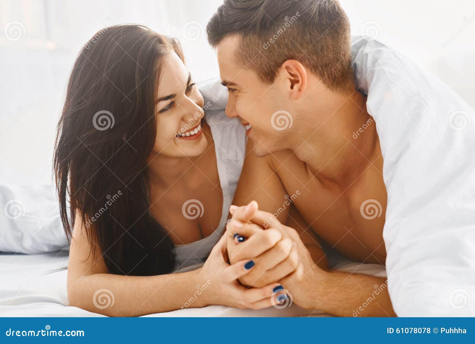 Закройте вверх по портрету романтичных пар в кровати
