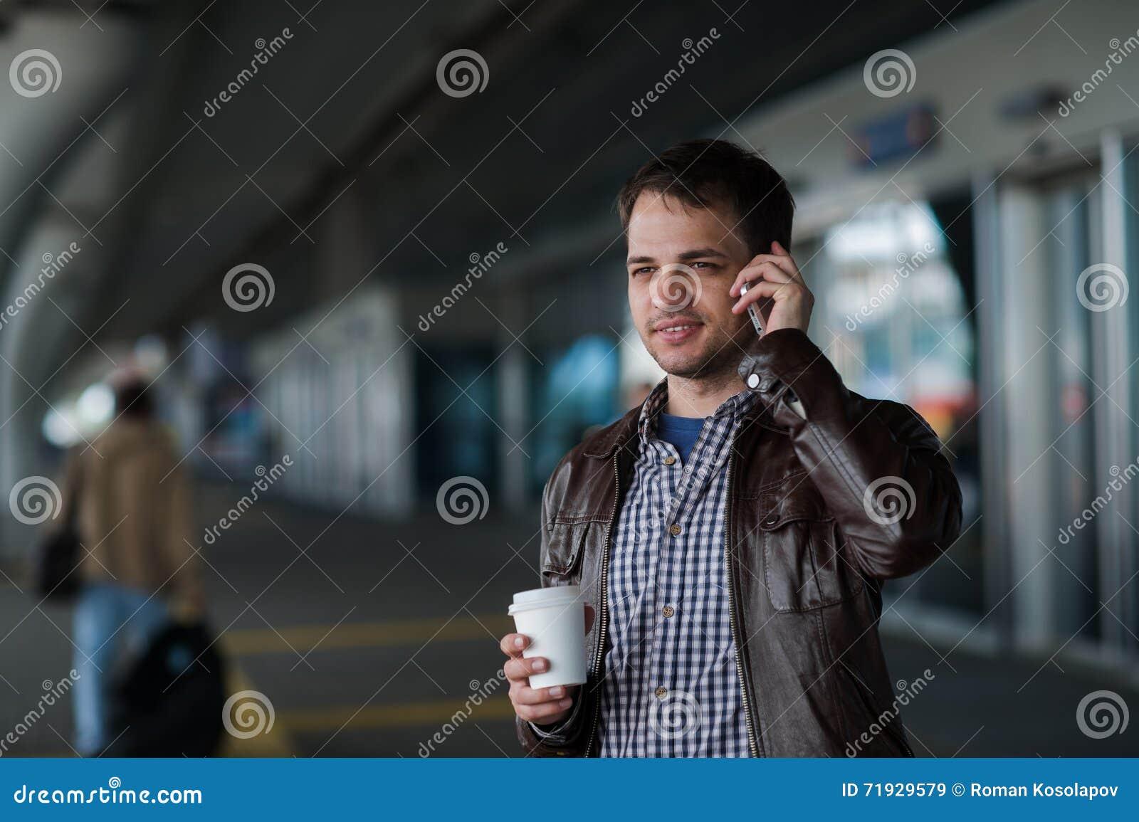 Закройте вверх по портрету серьезного молодого человека говоря на мобильном телефоне около крупного аэропорта с кофе