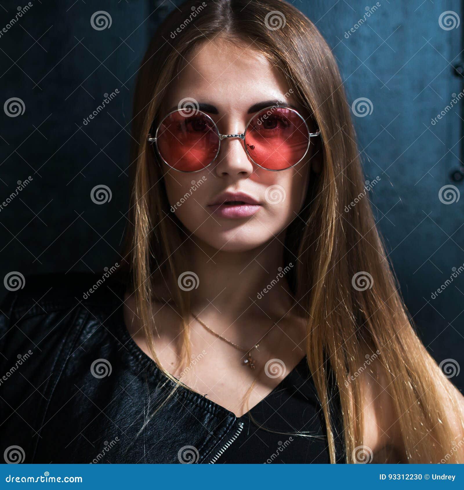 Закройте вверх по портрету стороны красивой кавказской молодой женщины с свободными волосами в модный розовый круглый смотреть со