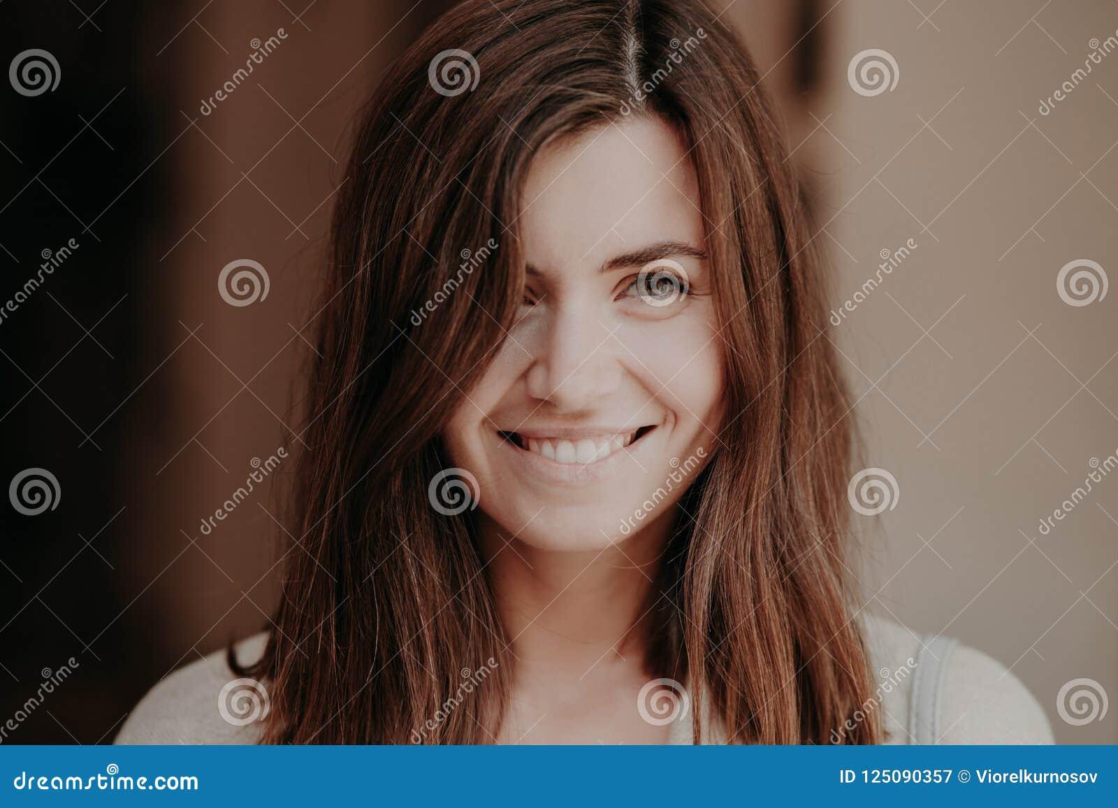 Закройте вверх по портрету счастливой женщины брюнет с зубастой улыбкой, взглядами счастливо на камере, здоровой коже, естественн