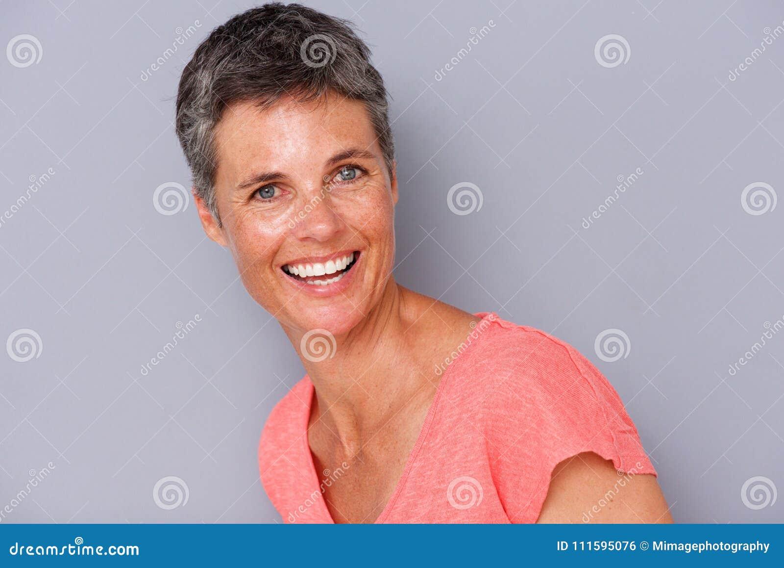 Закройте вверх по привлекательной женщине среднего возраста смеясь над серой предпосылкой