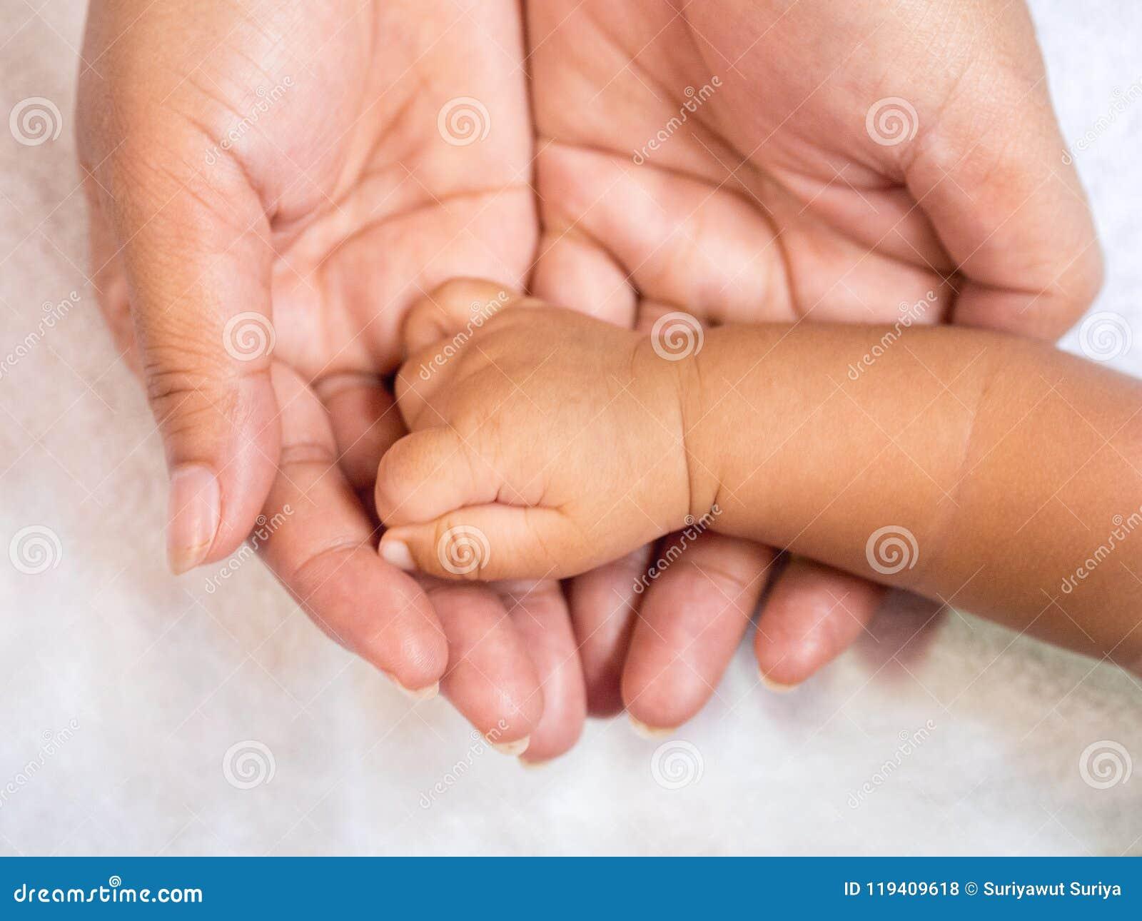 Закройте вверх по руке младенца на руках ` s матери Концепция влюбленности и семьи