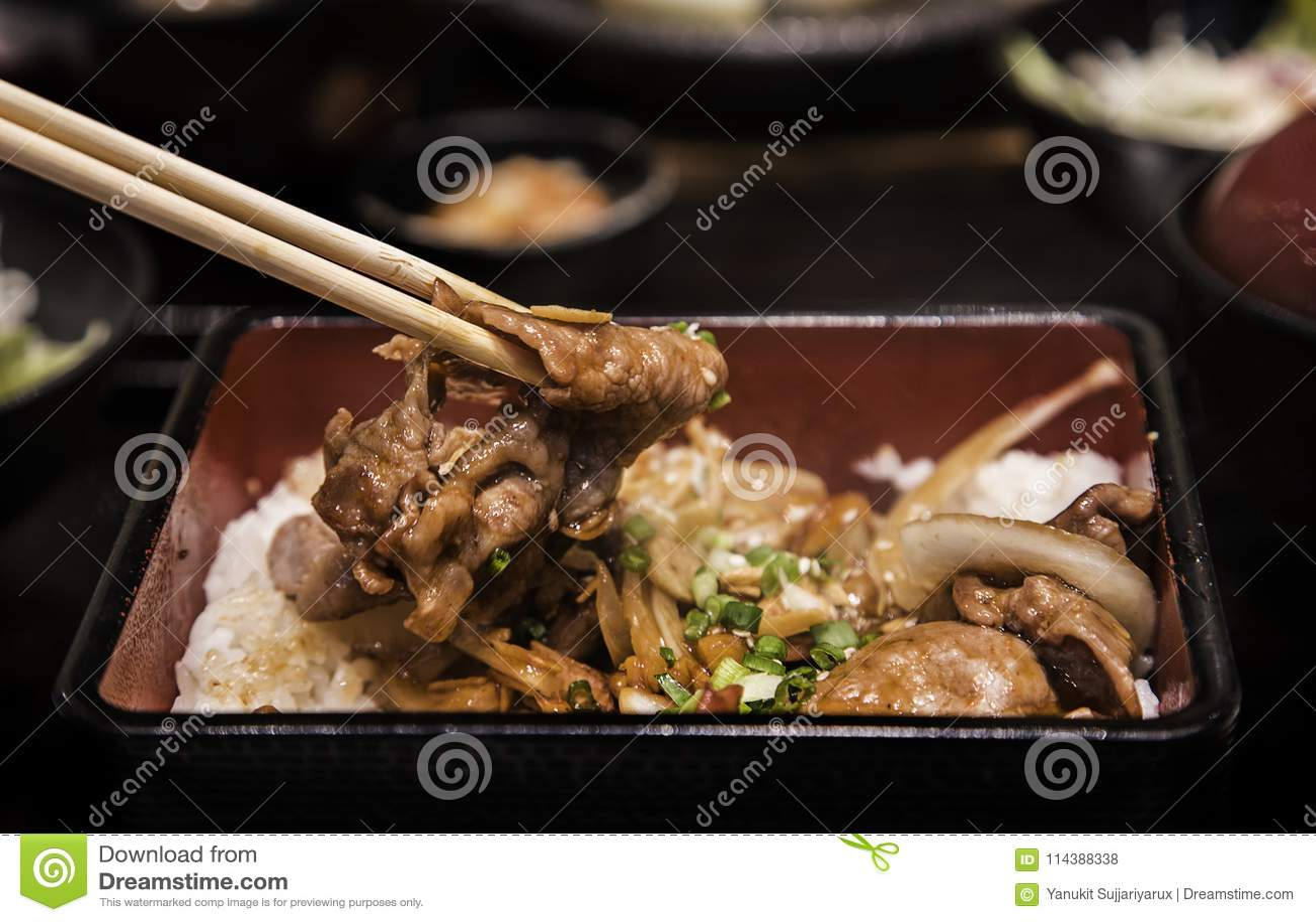 Закройте вверх по свинине гриля с луком и чесноком в еде японца boxet