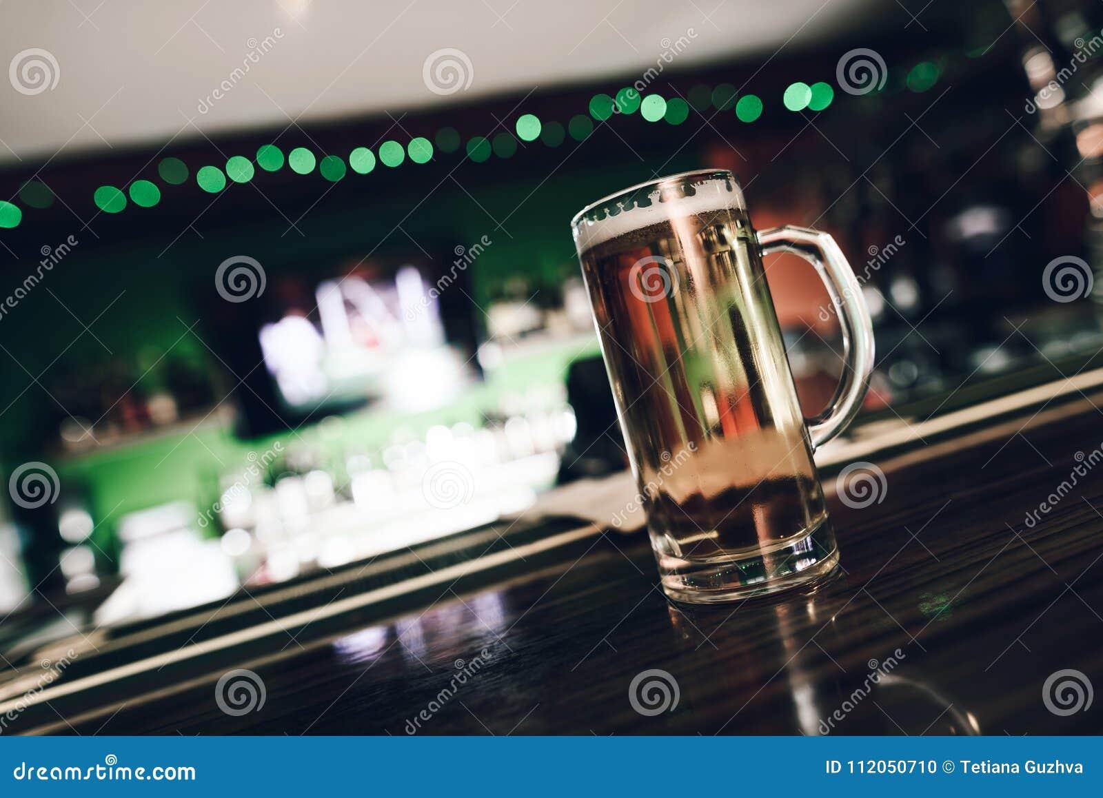 Закройте вверх по стеклу пива стоя на таблице бара на баре спорт