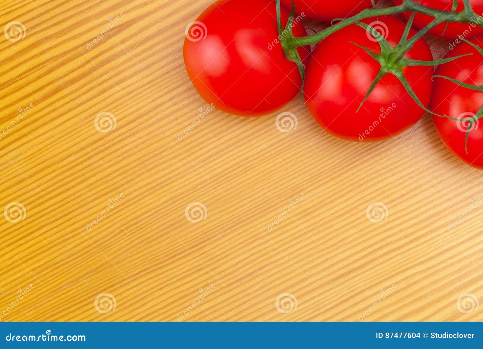 Закройте вверх по студии снятой пука томатов на деревянном столе