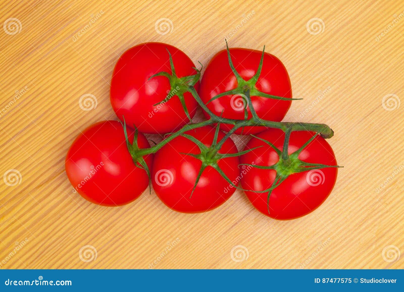 Закройте вверх по съемке пука томатов на деревянном столе