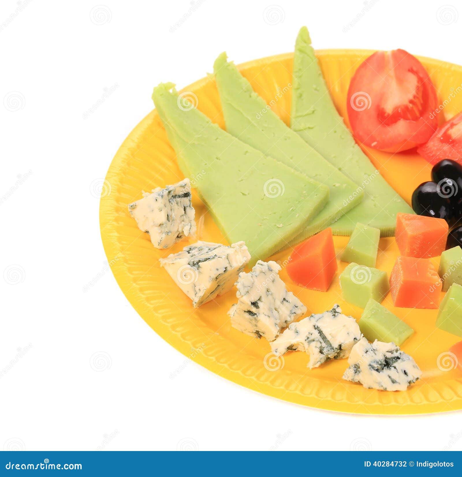 Закройте вверх различного сыра на желтом диске