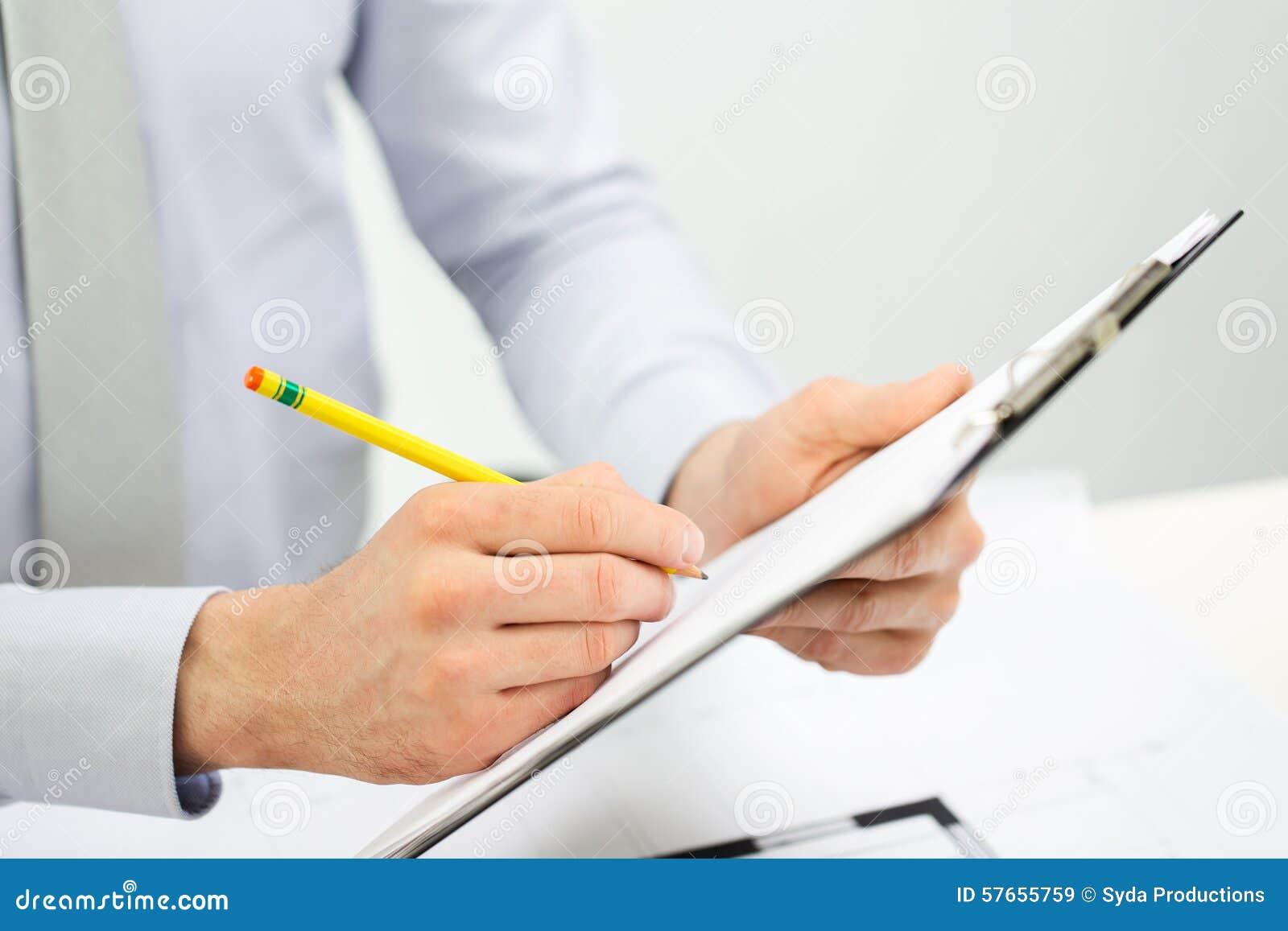 Закройте вверх рук бизнесмена с доской сзажимом для бумаги