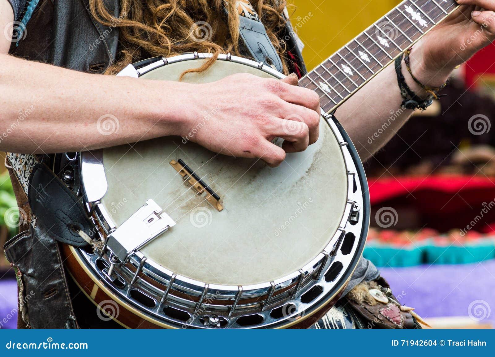 Закройте вверх рук игроков банджо играя банджо на рынке фермеров