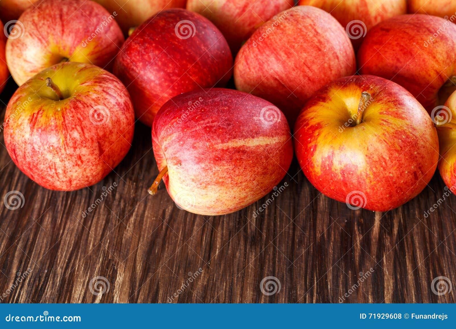 Закройте вверх свежих яблок на деревянной предпосылке