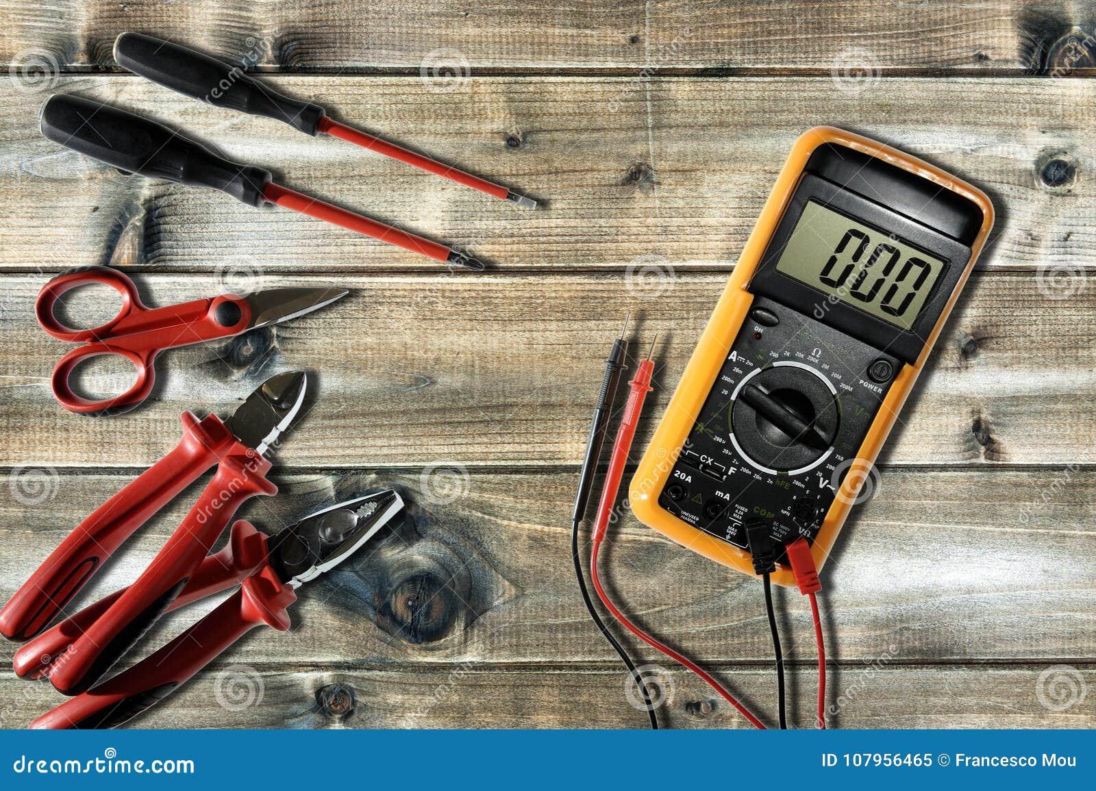 Закройте вверх сверху инструментов работы на электрических установках, на античный деревянный стол