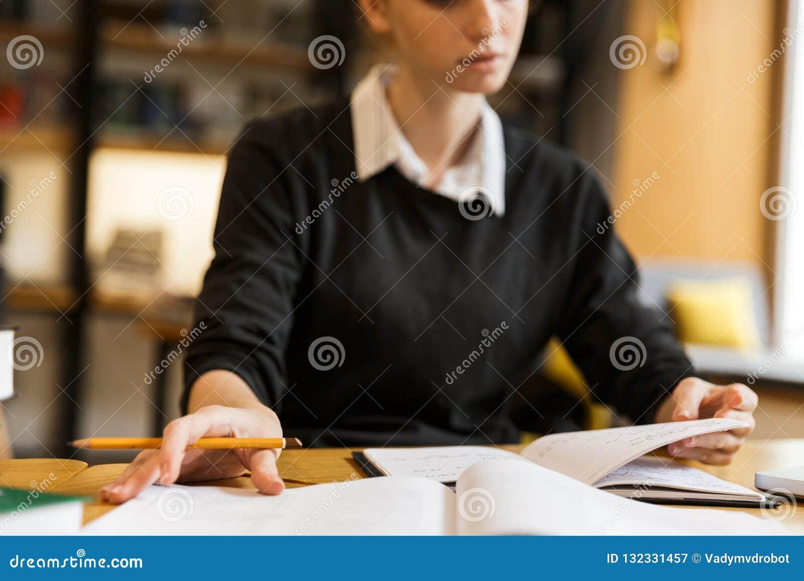 Закройте вверх сконцентрированный изучать девочка-подростка