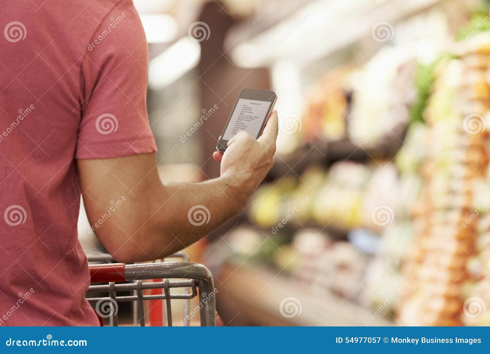 Закройте вверх списка покупок чтения человека от мобильного телефона в супермаркете