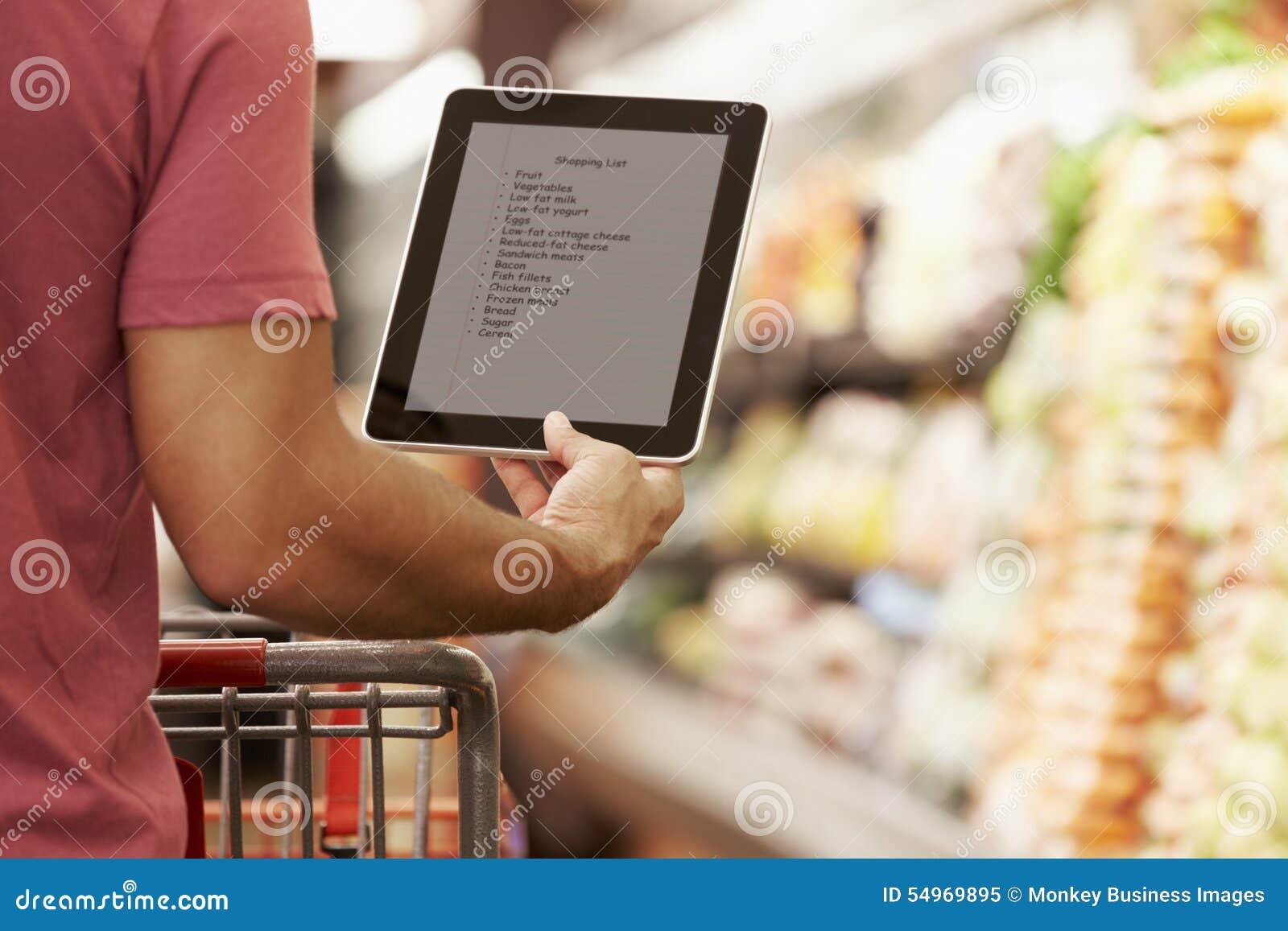 Закройте вверх списка покупок чтения человека от таблетки цифров в супермаркете