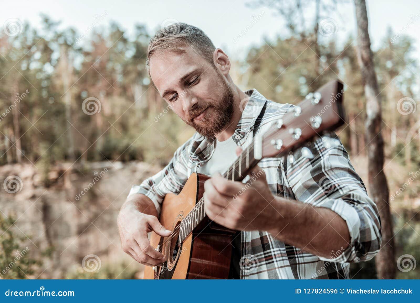 Закройте вверх счастливого красивого бородатого человека играя гитару сидя около гор